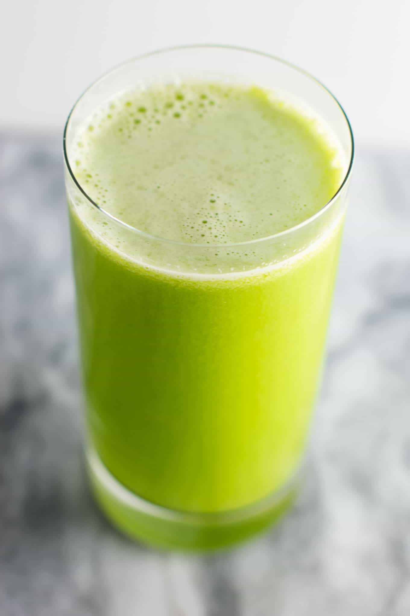 Easy cleansing green juice recipe made with cucumbers, lemons, celery, apples and romaine lettuce. #greenjuice #cleansinggreenjuice #juicing #vegan