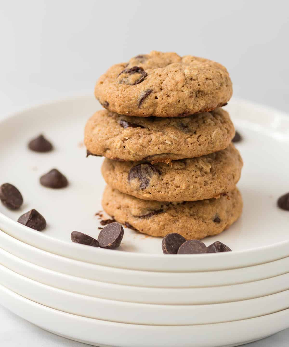 four whole wheat chocolate chip cookies stacked on a white plate