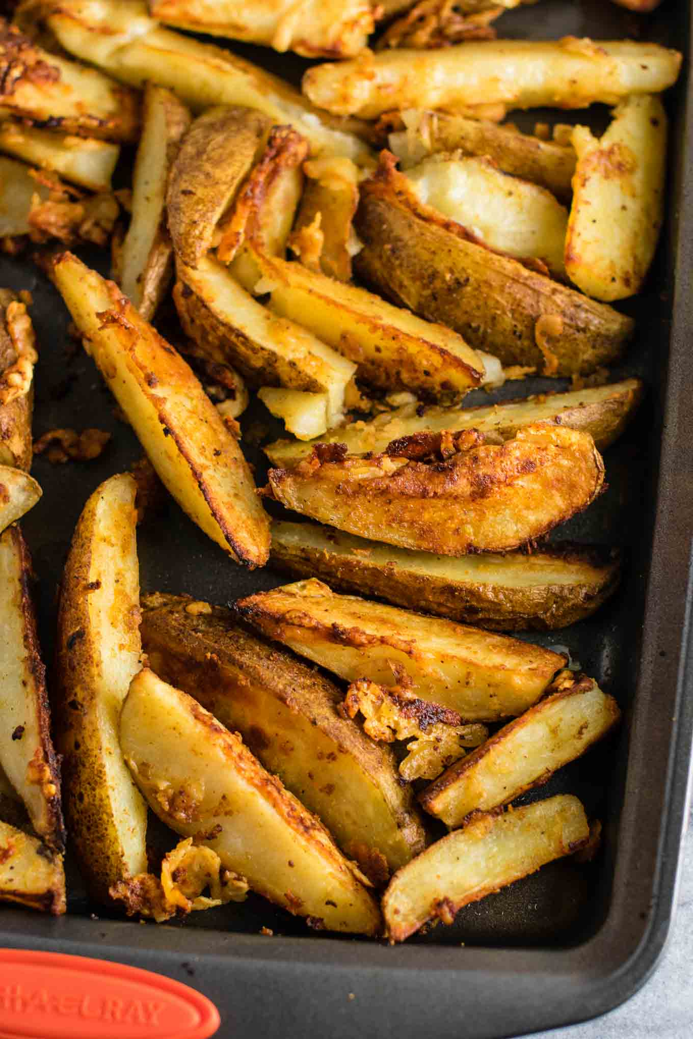 baked parmesan potato wedges - freshly grated parmesan gives these those amazing crispy edges. Perfect easy side dish! #garlicparmesan #potatowedges #sidedish #vegetarian #parmesan #dinner