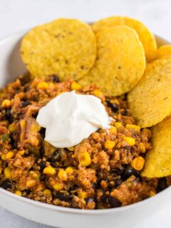 mexican quinoa enchilada bake in a bowl with sour cream and chips