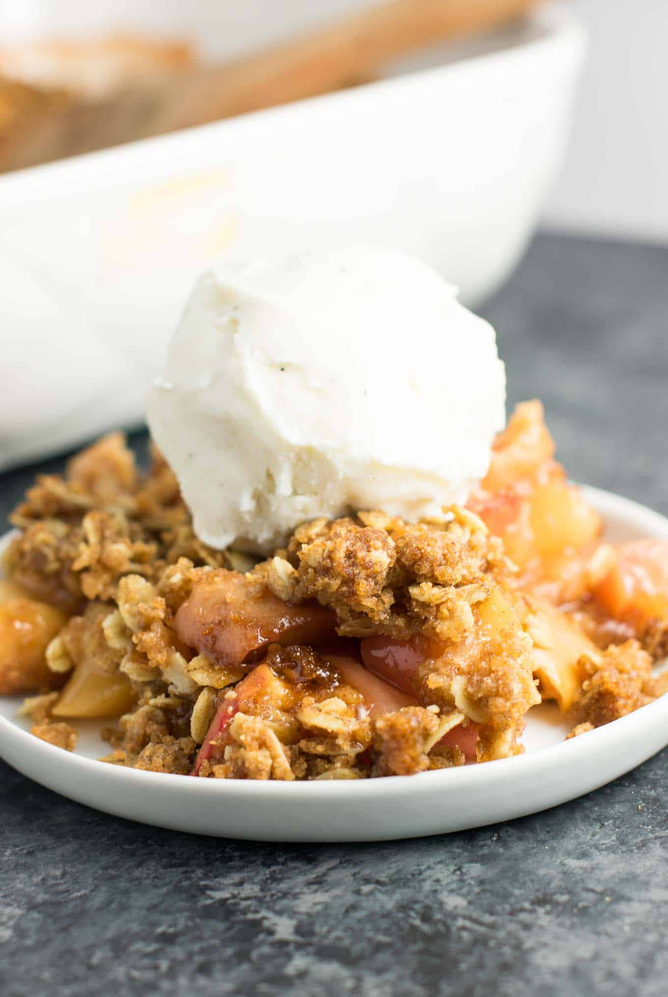 vegan apple crisp on a plate with a scoop of vanilla ice cream on top
