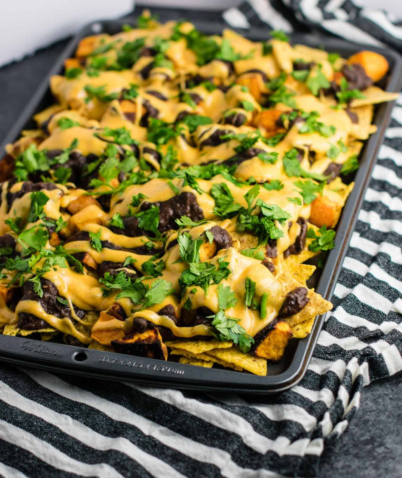 30 minute sweet potato refried bean nachos with homemade refried beans and cheese sauce. An impressive vegetarian dinner made in less than half an hour! #vegetarian #sweetpotatonachos #30minutemeal