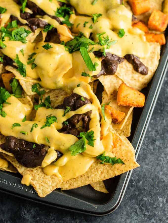 30 minute sweet potato refried bean nachos with homemade nacho cheese sauce. This is our go to Mexican meal! #30minute #vegetarian #sweetpotatonachos #sweetpotato #glutenfree #nachocheesesauce