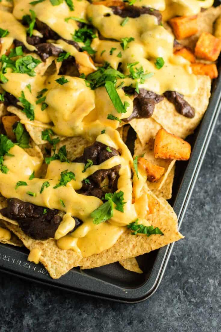 30 minute sweet potato refried bean nachos with homemade nacho cheese sauce. This is our go to Mexican meal! #30minute #vegetarian #sweetpotatonachos #sweetpotato #glutenfree #nachocheesesauce