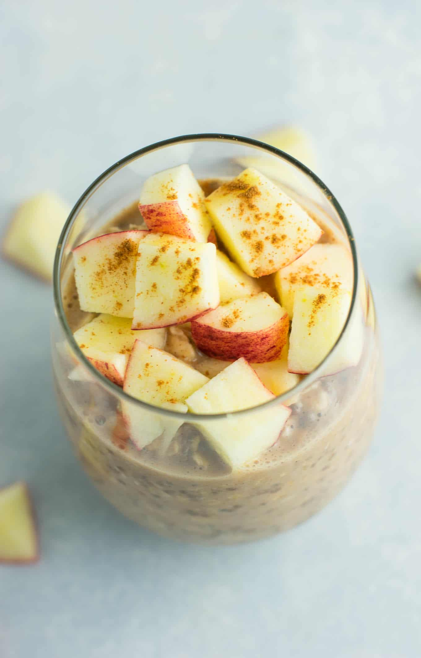 overnight oats in a glass topped with chopped apples and cinnamon