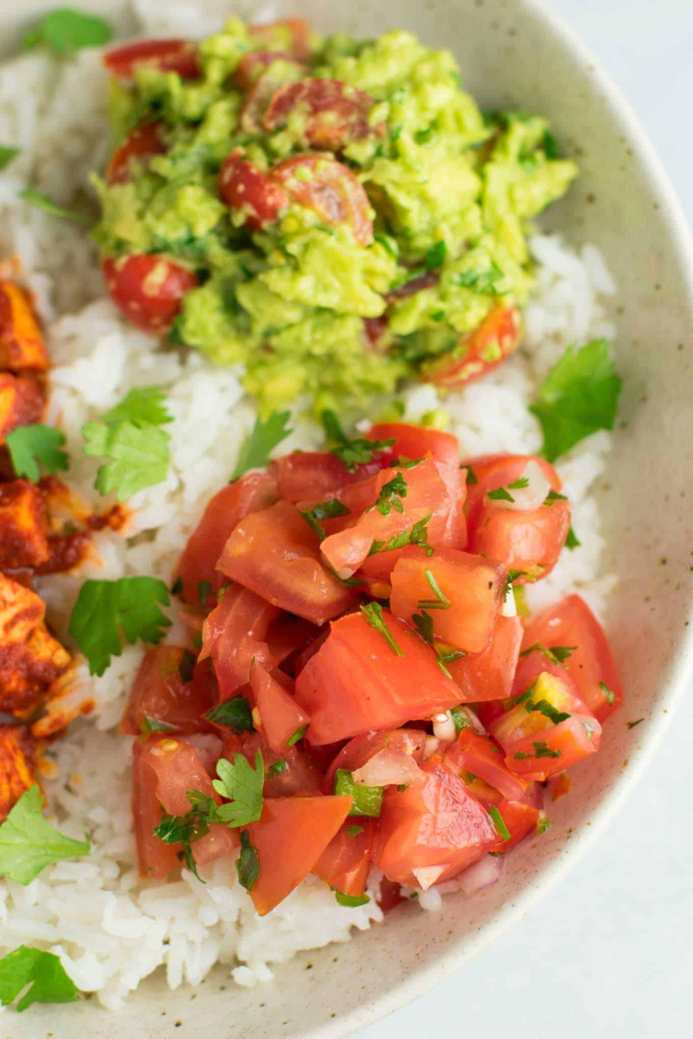 Easy enchilada tofu burrito bowls with homemade guacamole and salsa. Bring chipotle to your kitchen with this delicious recipe! #vegan #burritobowls #tofuburritobowls
