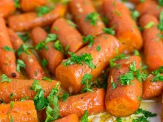Garlic butter roasted carrots recipe with fresh parsley. A delicious vegan friendly side dish recipe that will disappear in minutes! #vegan #roastedcarrots #garlicbutter #garlicbuttercarrots #sidedishes #vegetables