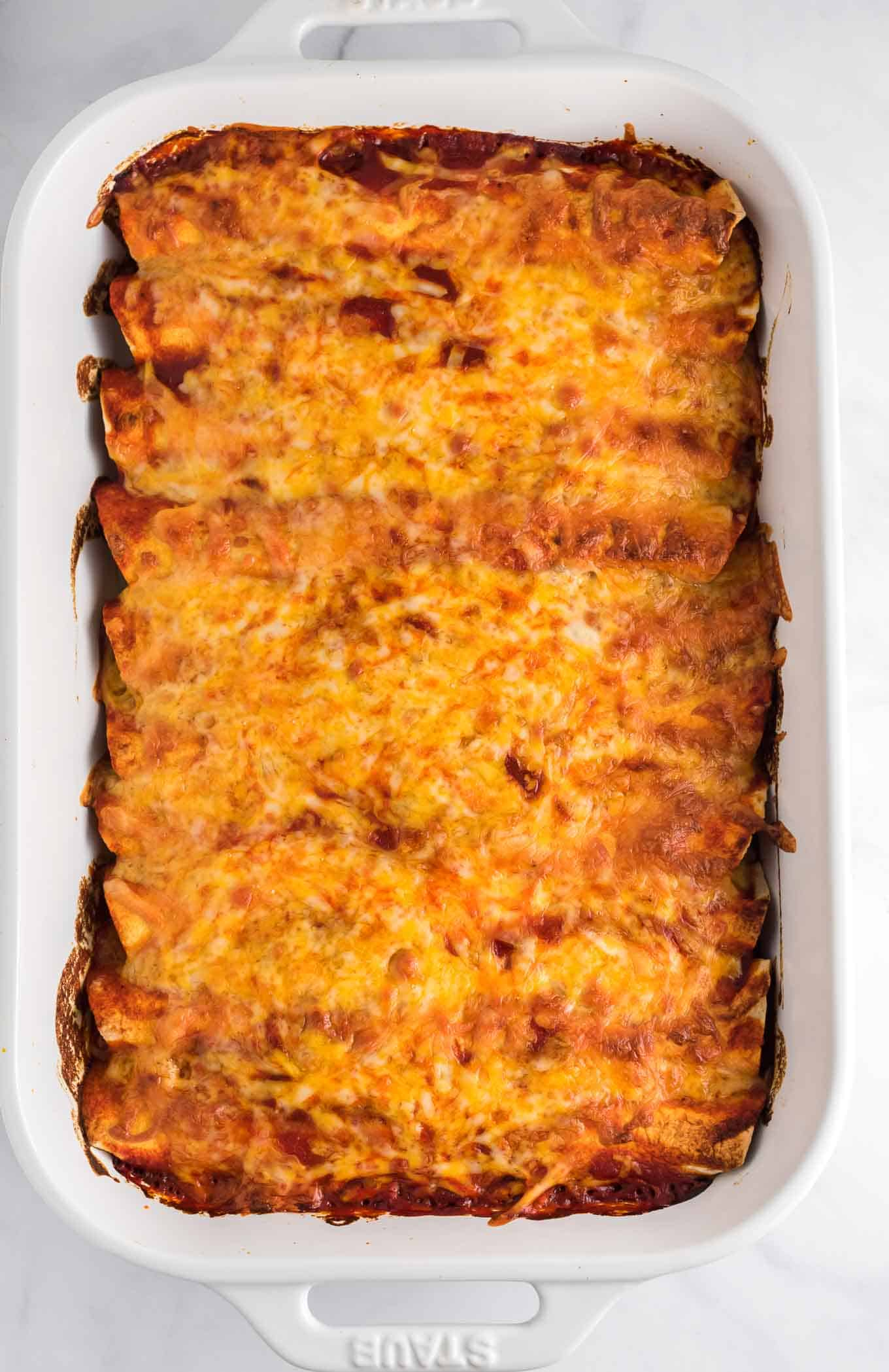 enchiladas in a white 9 by 13 pan