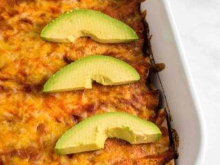 enchiladas with sliced avocado from a side angle
