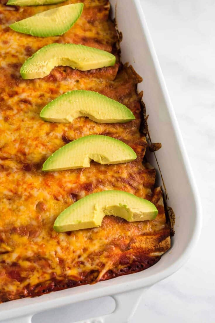 enchiladas with sliced avocado from a side angle