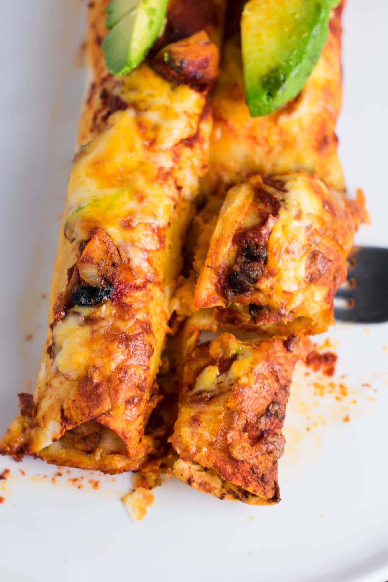 Smoky Sweet potato black bean enchiladas recipe. Even meat eaters will flip for these delicious enchiladas covered in sauce and freshly grated Colby jack. #meatless #dinner #vegetarian #enchiladas