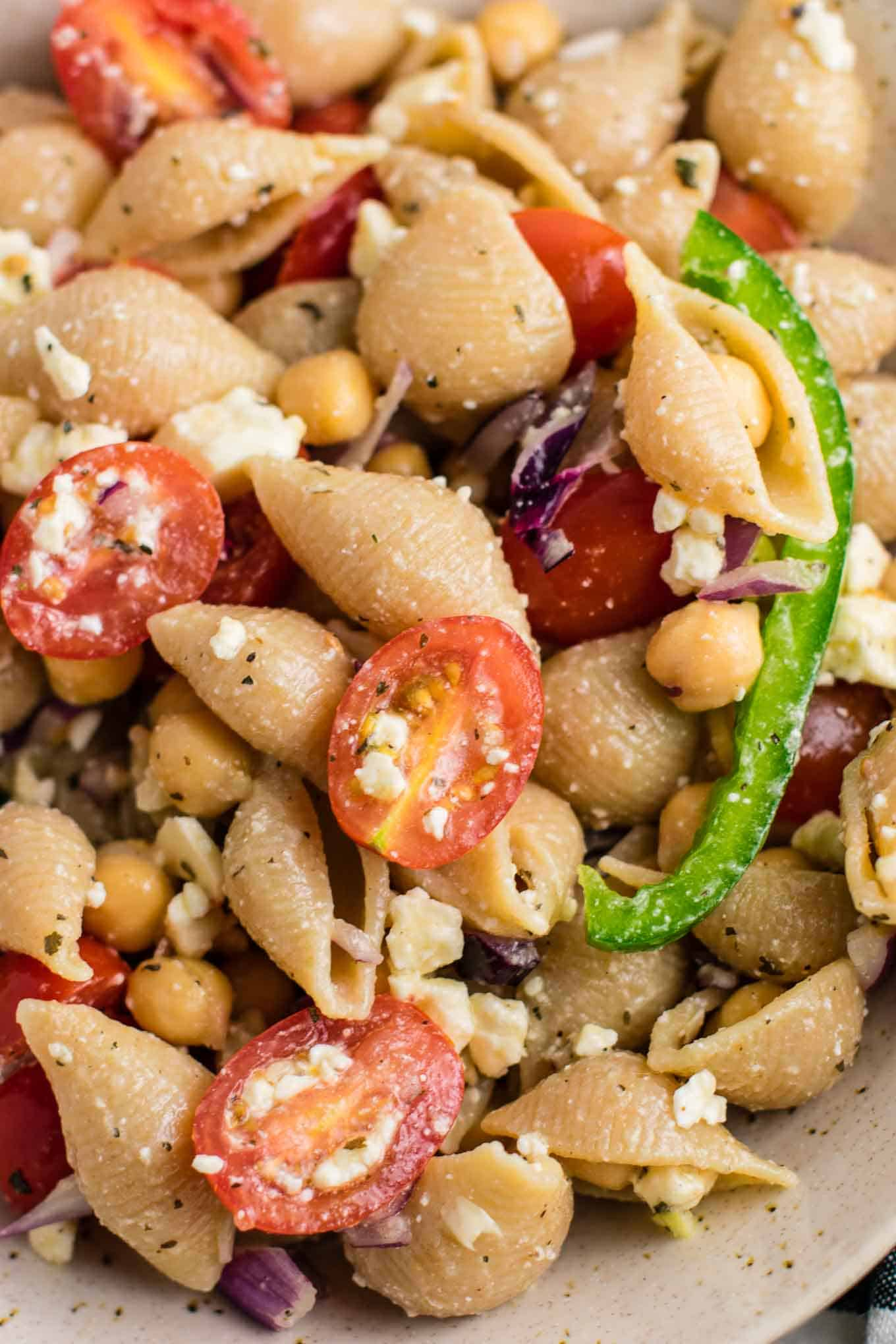 This Chickpea Pasta Salad with whole wheat pasta is an easy vegetarian pasta salad recipe. Perfect to take to parties, or as a healthy meal prep lunch. So addicting and full of good for you ingredients! #vegetarian #pastasalad #chickpea #feta #vegetarianpastasalad