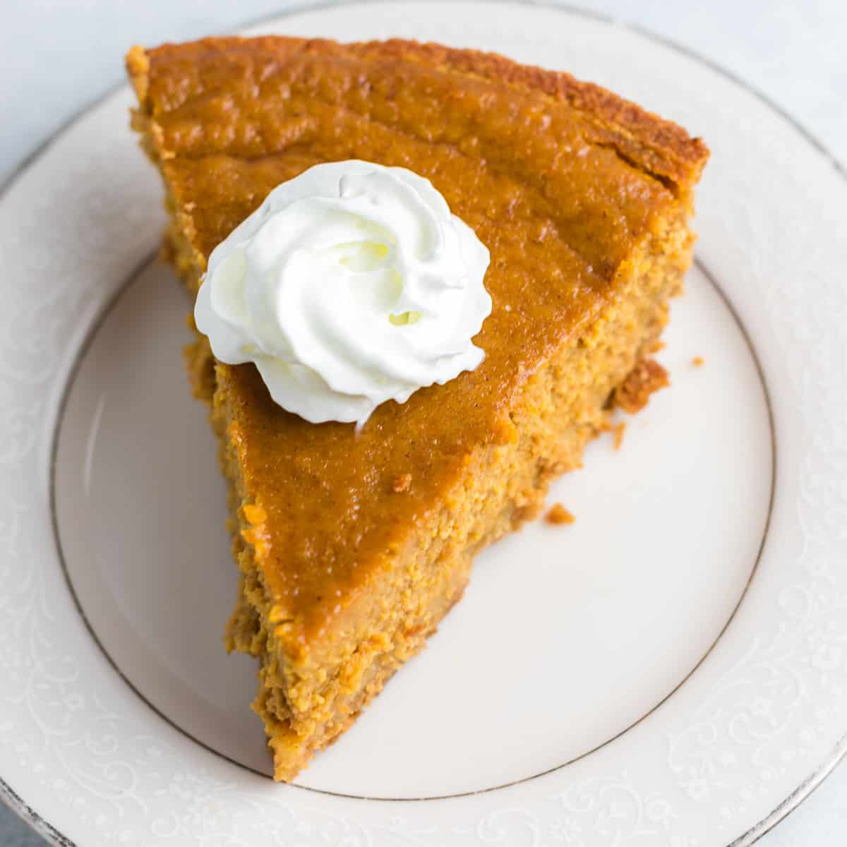 a slice of pumpkin pie on a plate topped with whipped cream
