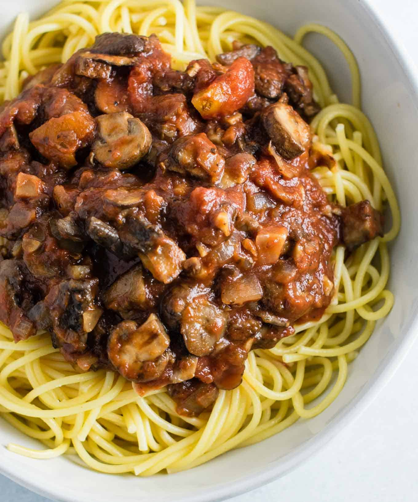 vegetarian mushroom spaghetti sauce over white spaghetti noodles in a white bowl
