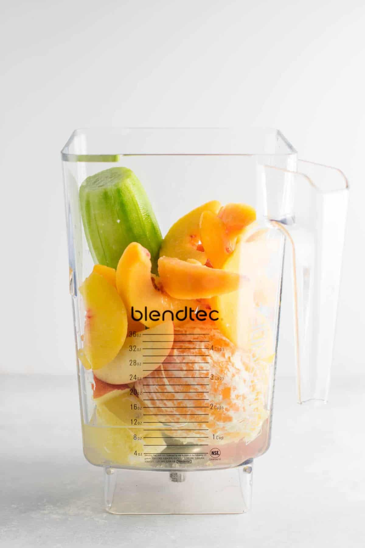 cucumber, peaches, apple, oranges, lemon, and water in a blender