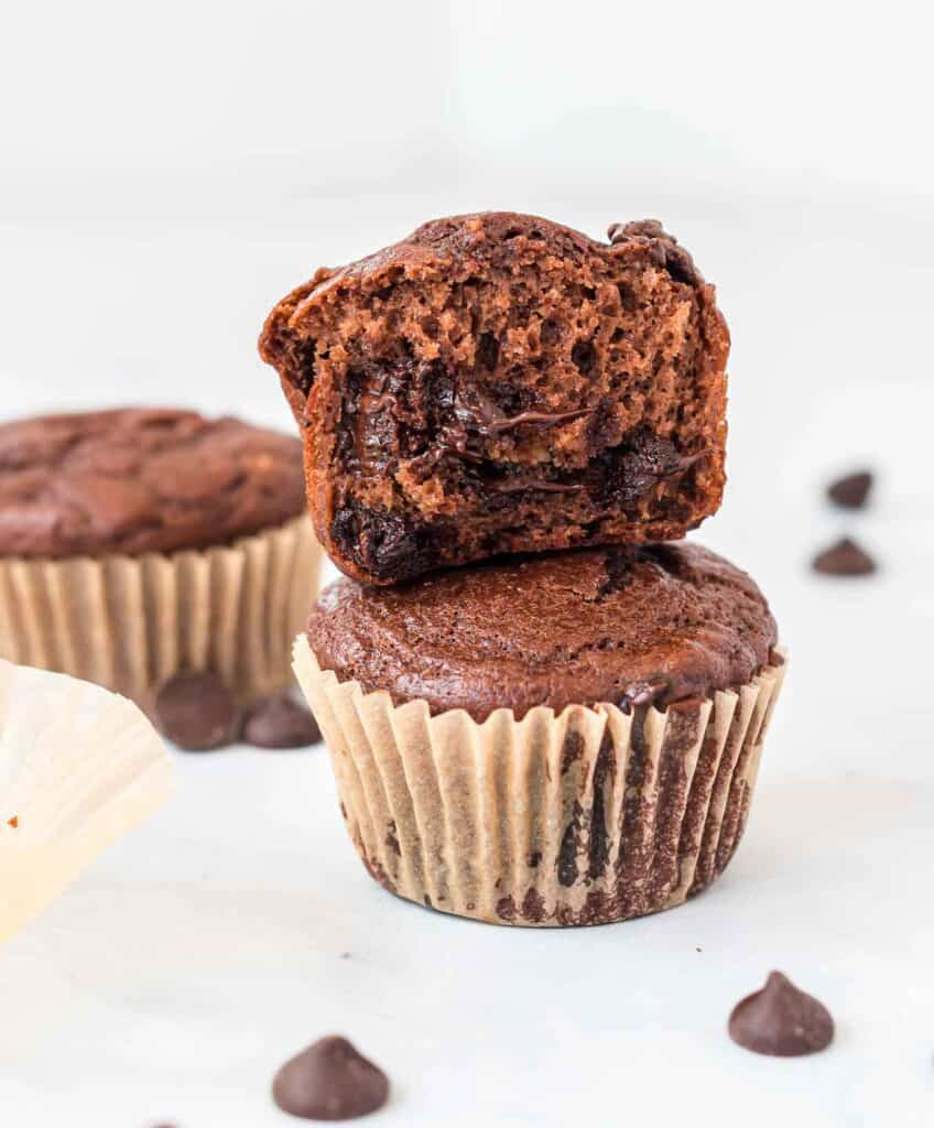 a chocolate muffin with a bite taken out stacked on top of another muffin
