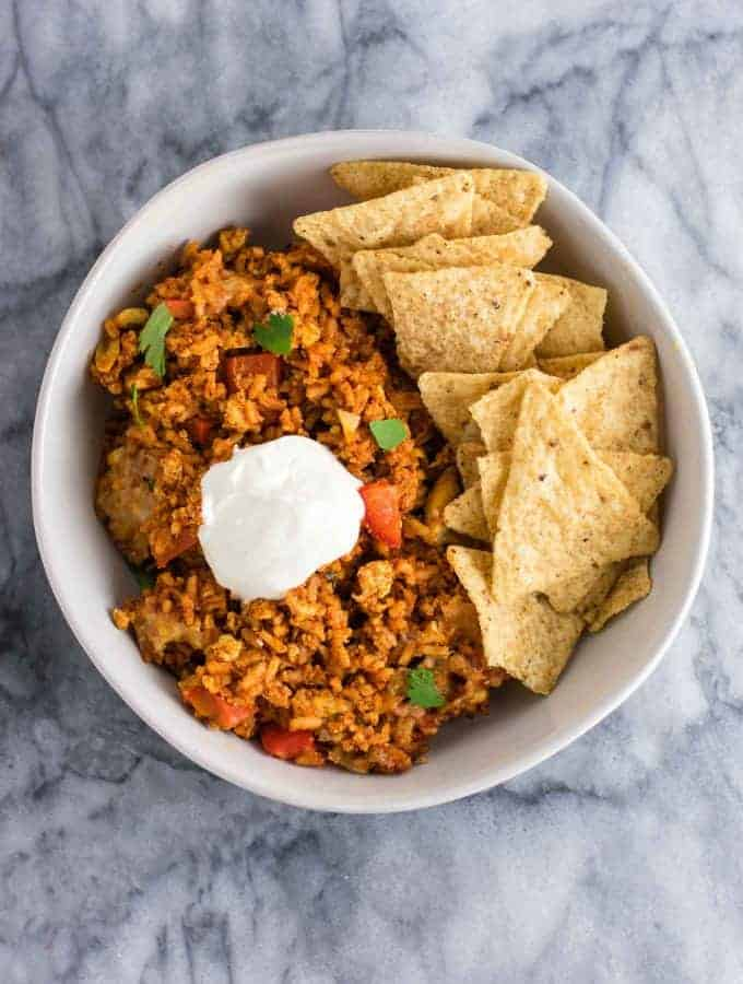 Tofu Mexican Rice Casserole Recipe with bell peppers and mushrooms. Scrambled tofu adds extra protein to this delicious vegetarian take on a healthier Mexican rice casserole. Serve with chips and sour cream! #tofumexicanrice #mexicanricecasserole #healthymexicanrice #tofu #vegetarian #dinner