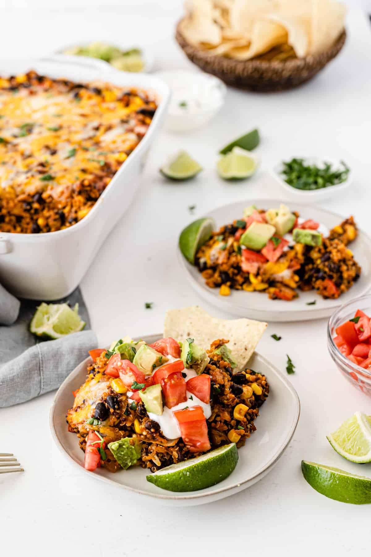 quinoa enchilada casserole on a white plate topped with sour cream, tomato, avocado, and lime