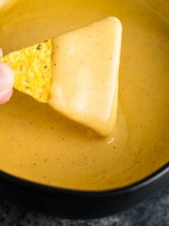 chip being dipped into nacho cheese