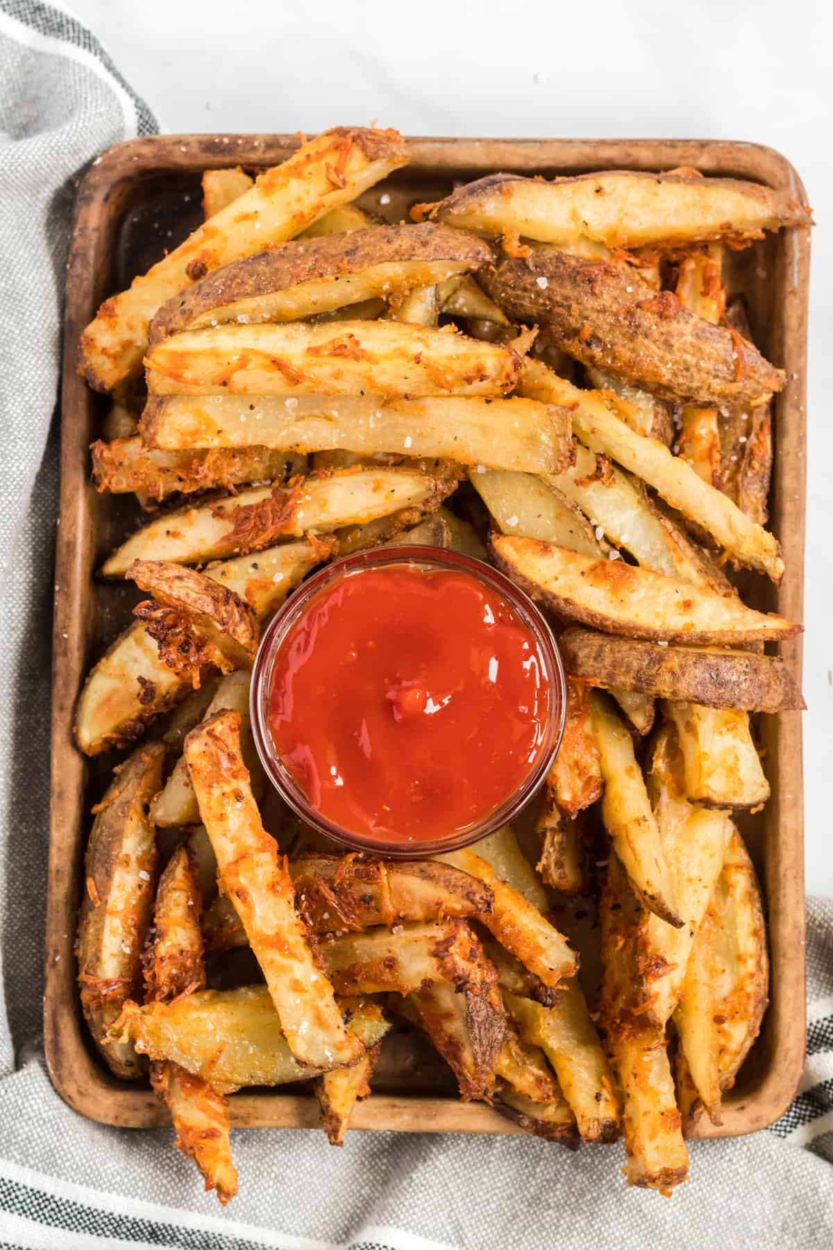 potato wedges on a brown serving tray with ketchup in the middle