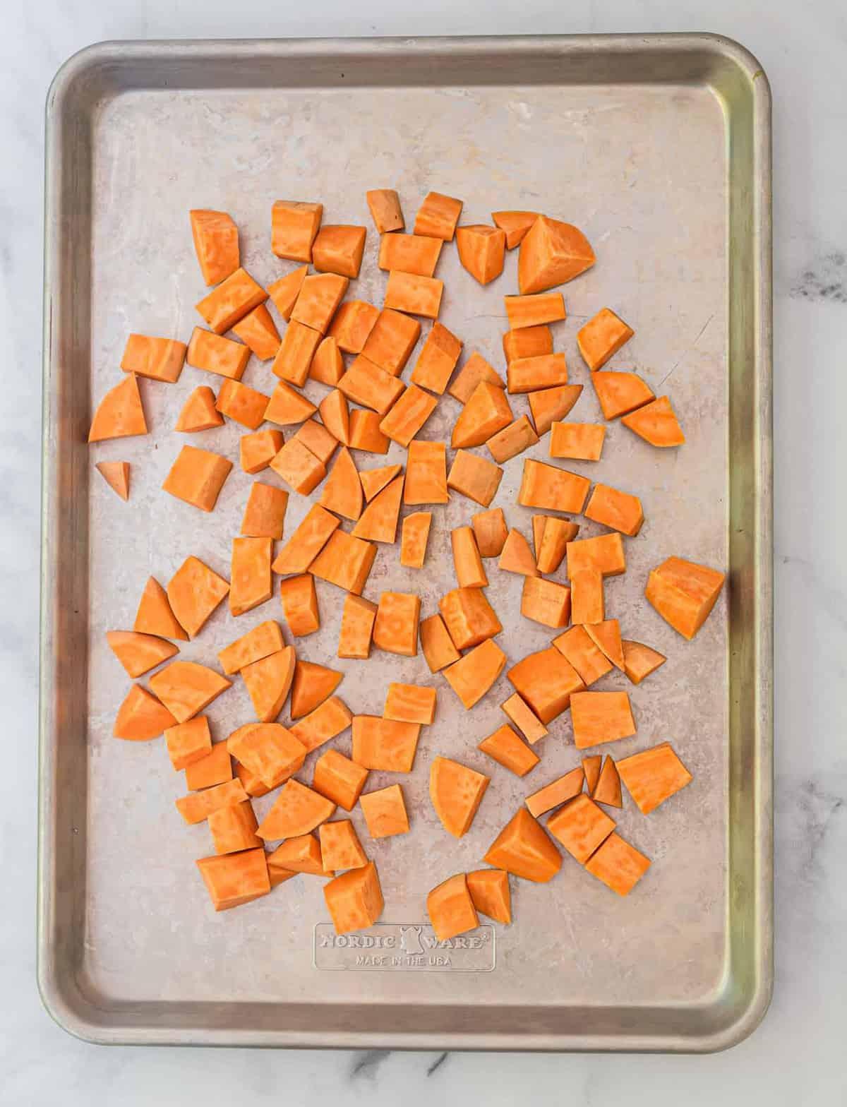 diced raw sweet potatoes on a baking sheet