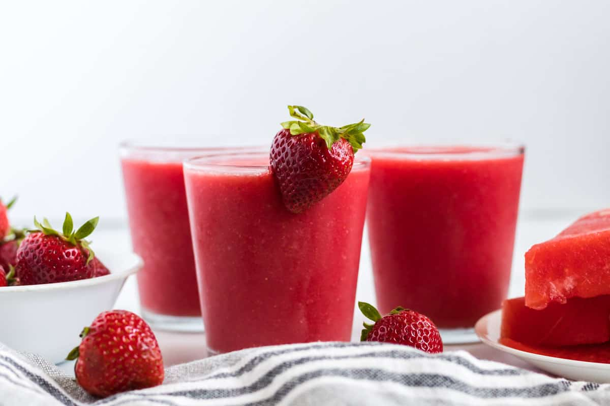 strawberry watermelon smoothie in a clear glass with a strawberry on the rim