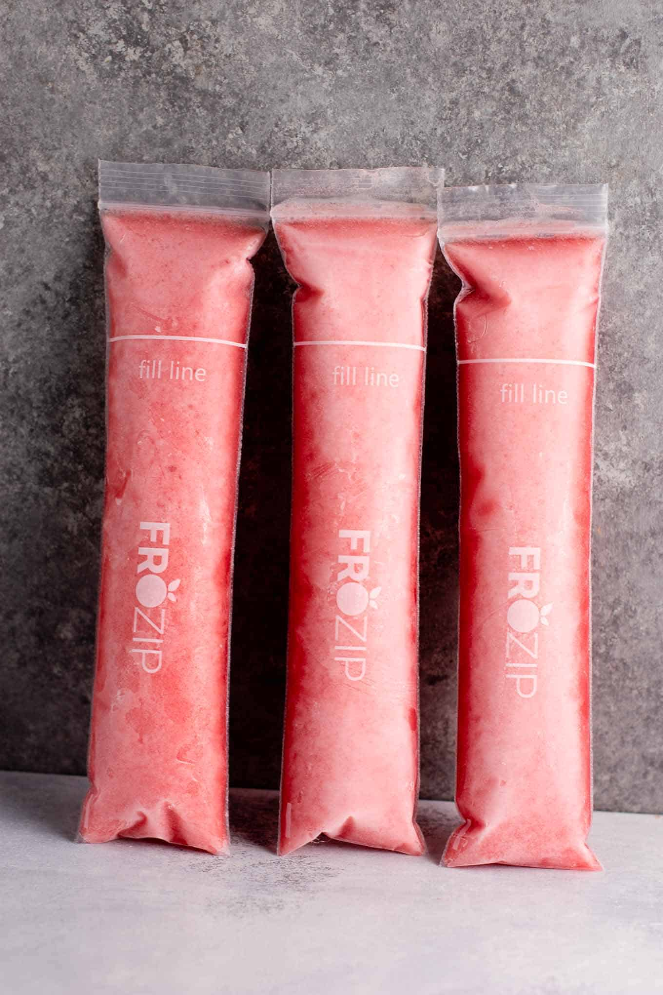 Strawberry pineapple freezer pops – learn how to make popsicles with just frozen fruit, coconut water and maple syrup! #freezerpops #healthy #icepops #popsicles #homemade #healthyrecipe #dessert #healthydessert #strawberrypineapple #summer