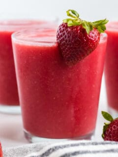 strawberry watermelon smoothie in a glass with a strawberry on the rim