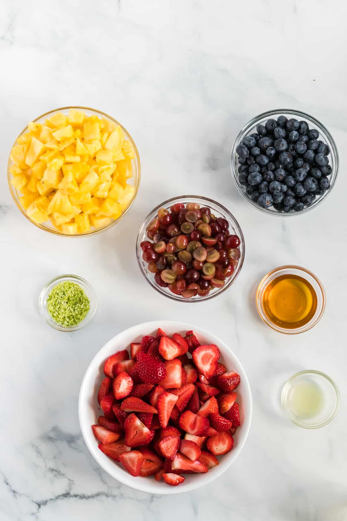 fruit salad ingredients in separate glass bowls