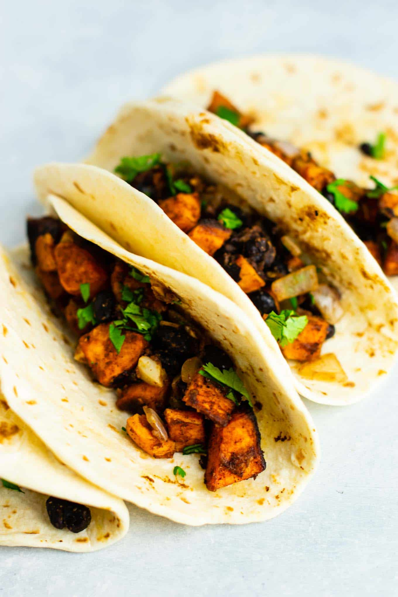 Sweet potato tacos with black beans and cilantro. Healthy, meatless, insanely delicious vegan dinner recipe! Serve with salsa and optional sour cream. #vegan #sweetpotatotacos #sweetpotatorecipes #sweetpotato #veganmexican #vegandinner #vegetarian #vegetariandinner #meatlessdinner #meatlesstacos #vegantacos