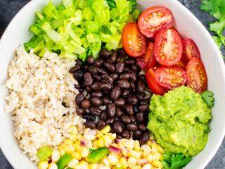 Vegan burrito bowl recipe with homemade fresh corn salsa and guacamole. Better than chipotle and so fresh and delicious! #vegan #burritobowl #meatless #chipotle #mexican #dinner #vegetarian #mealprep #dairyfree #guacamole #cornsalsa