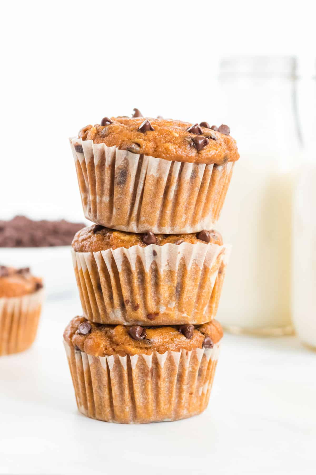 pumpkin chocolate chip muffins stacked on top of each other