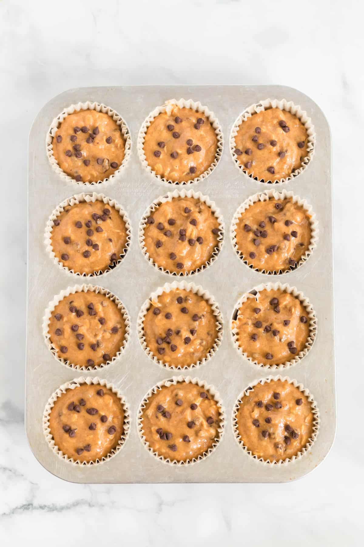 pumpkin muffin batter in lined muffin tins