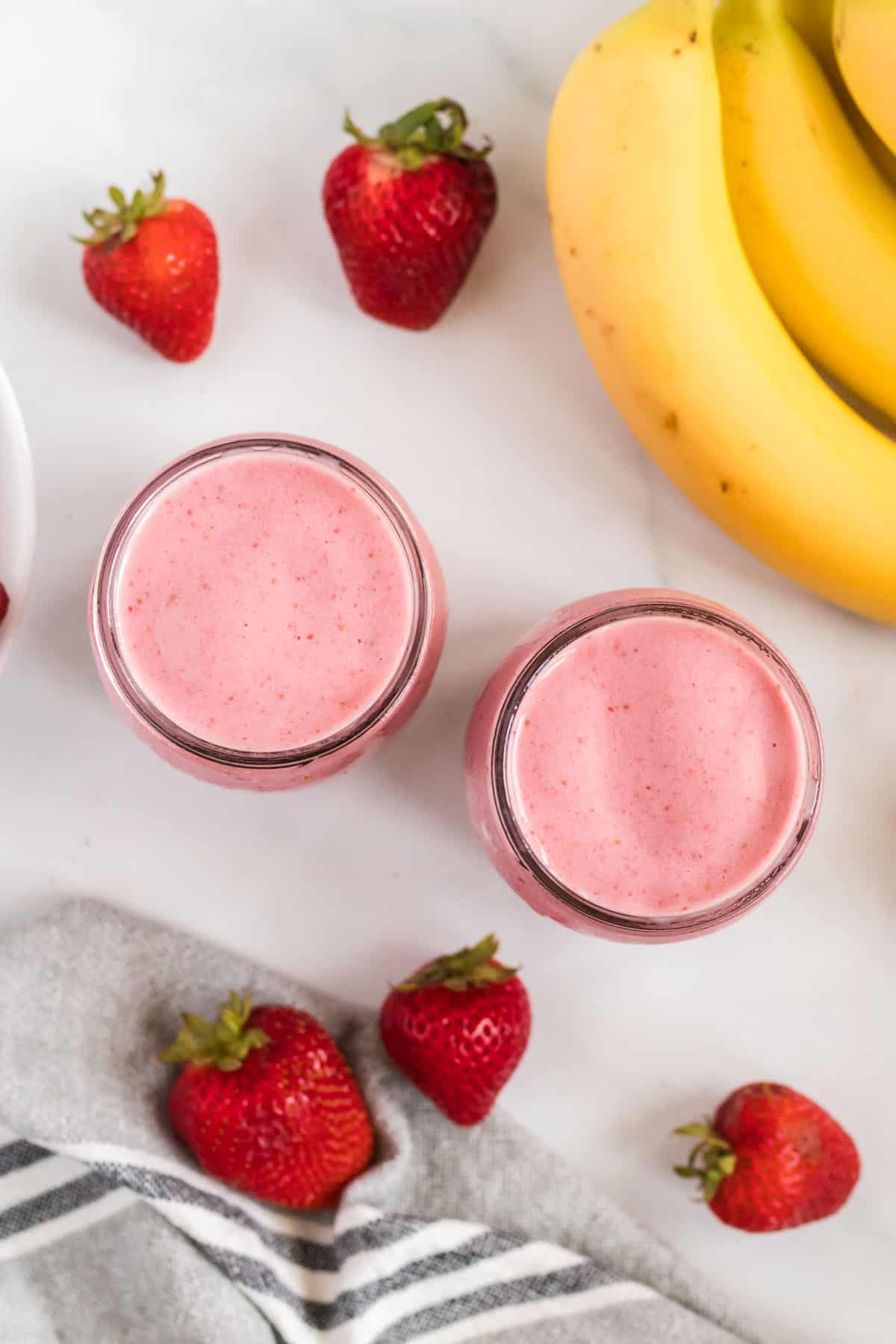 smoothies in glass jars from an overhead view surrounded by strawberries and bananas