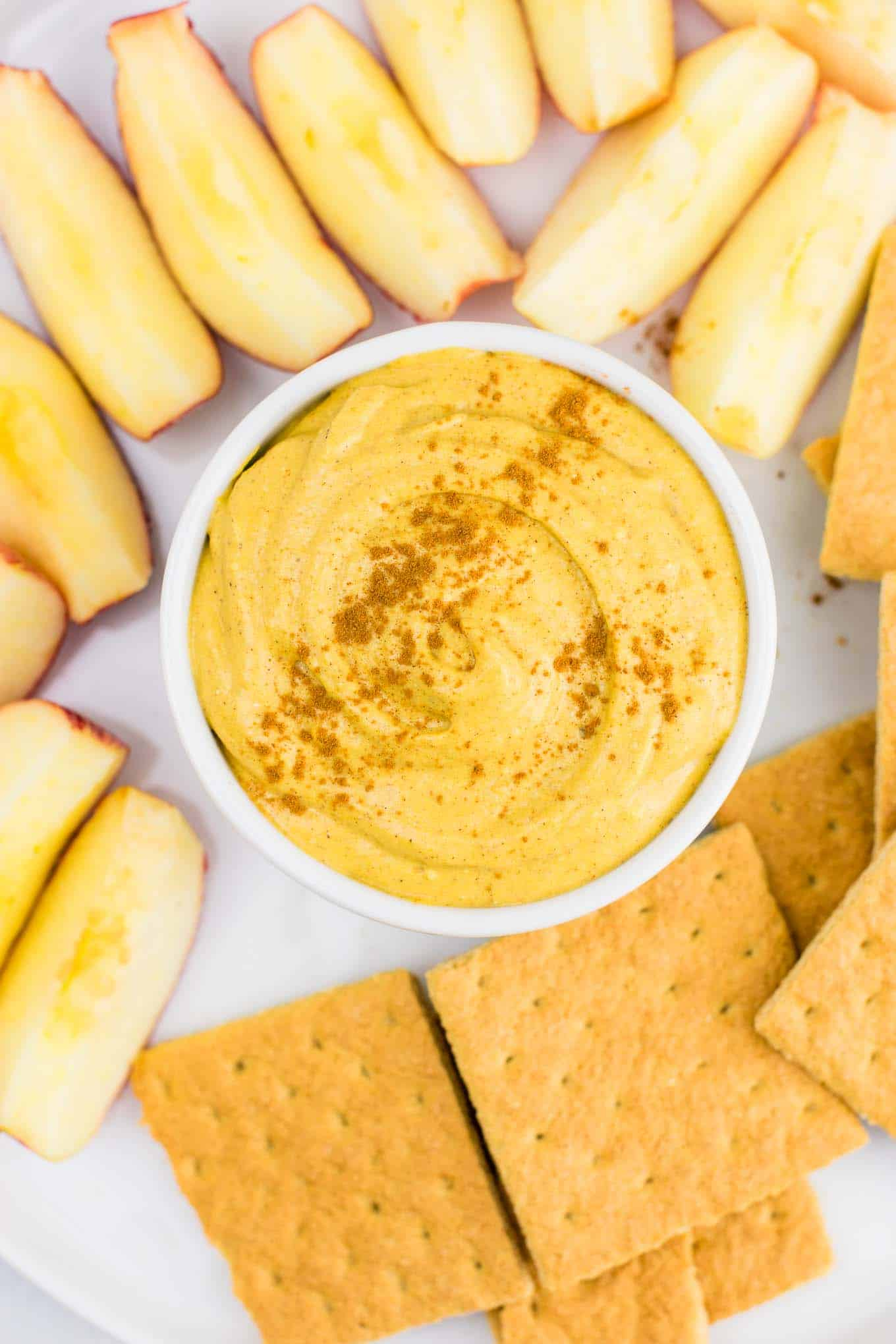 pumpkin dip sprinkled with cinnamon on a platter with apples and graham crackers