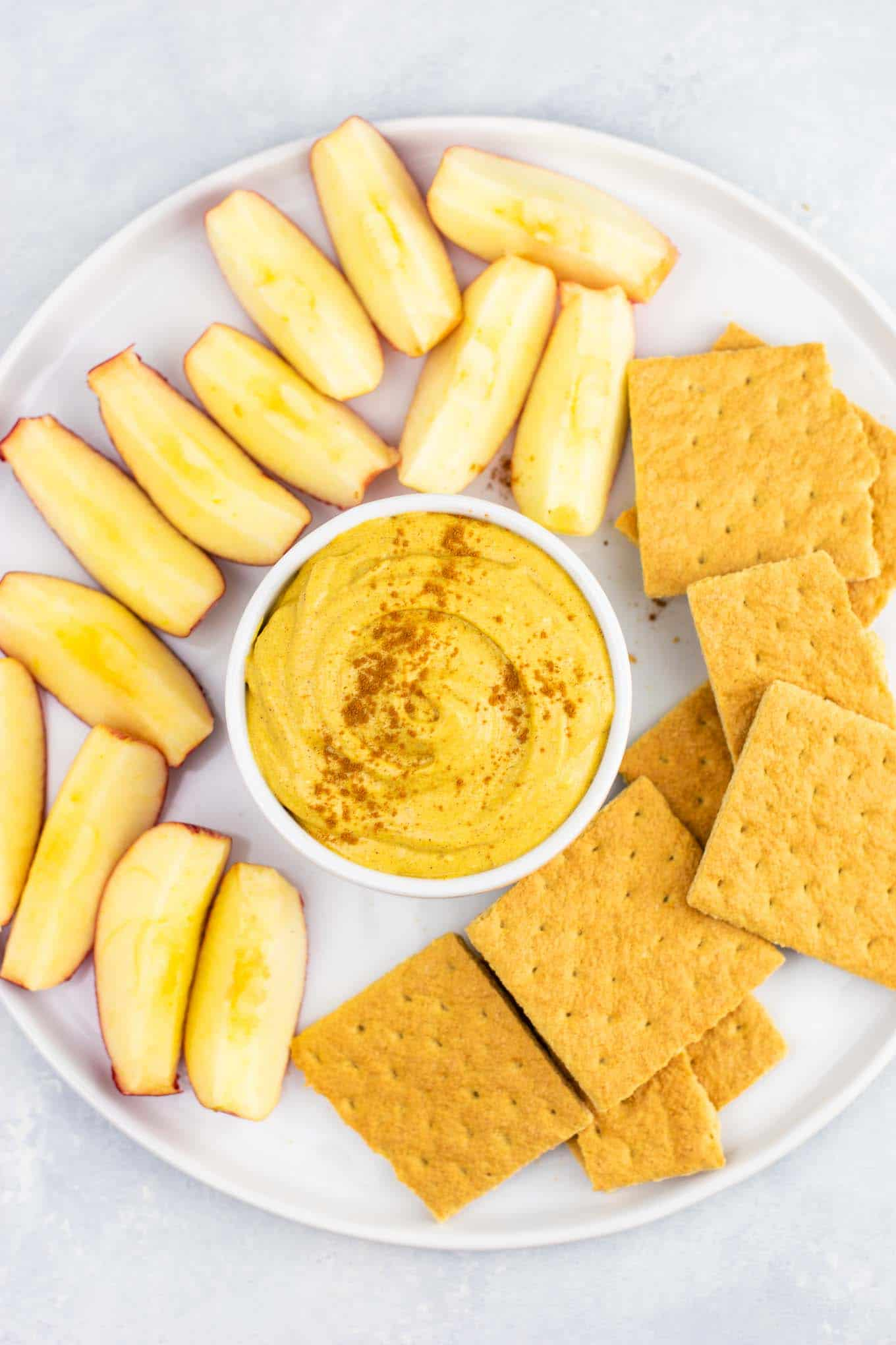 overhead view of the pumpkin dip on a platter surrounded by sliced apples and graham crackers