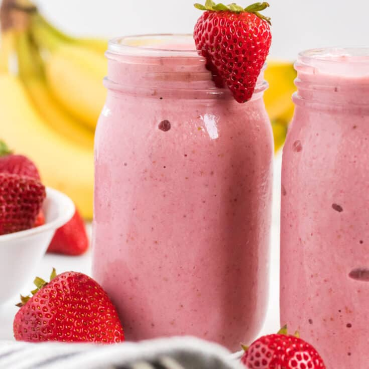 strawberry banana smoothie in a mason jar with a strawberry on the rim