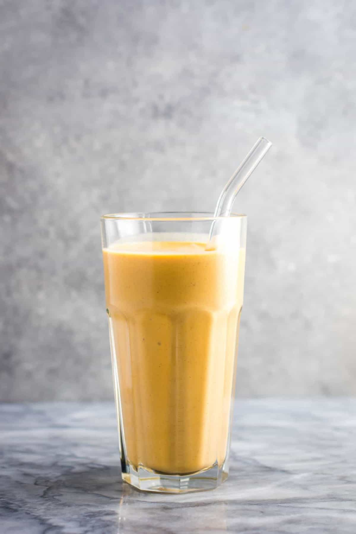 Sweet potato smoothie in a glass with a glass straw
