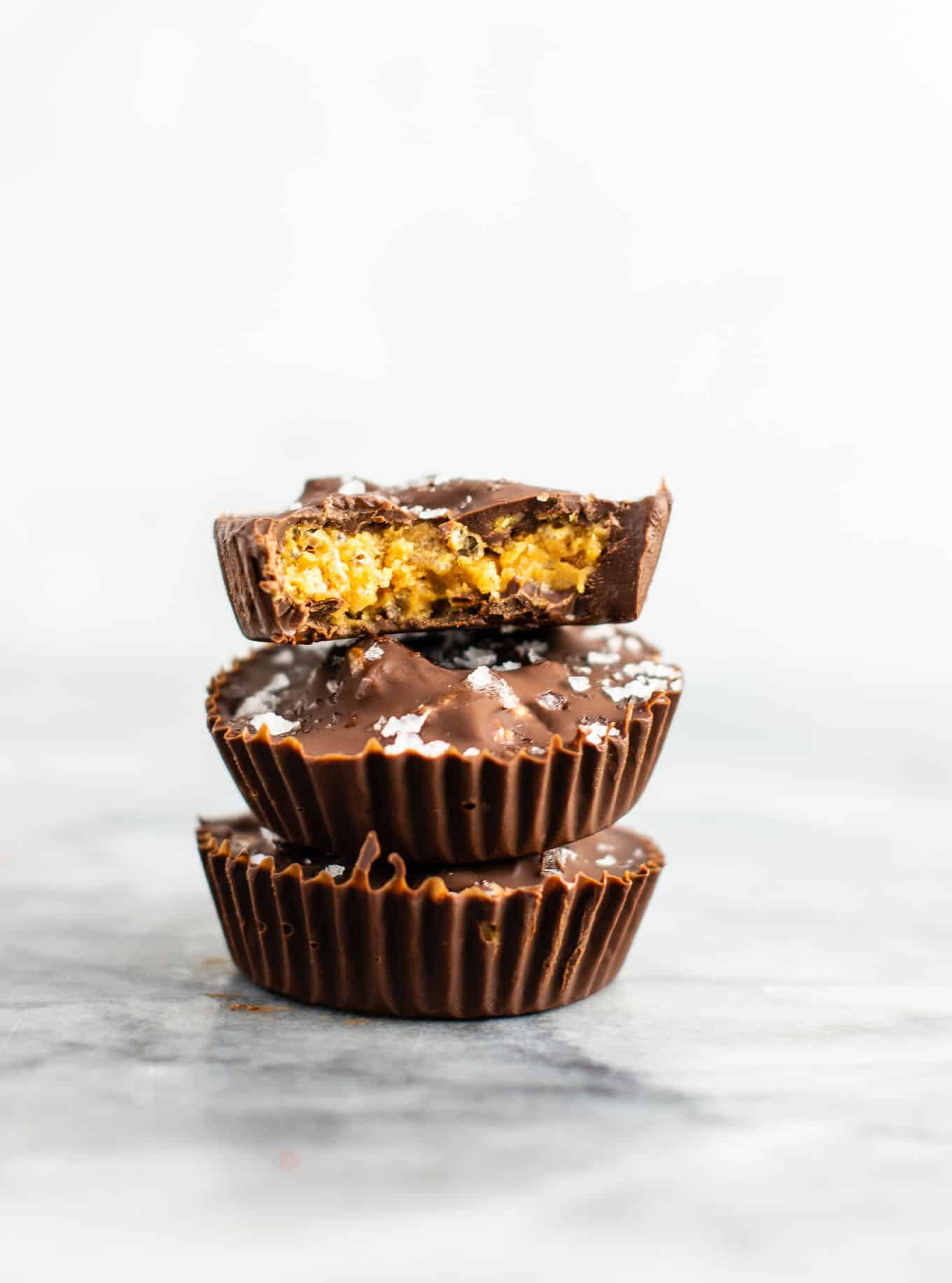 Chocolate peanut butter crunch cups with flaked sea salt – these are next level DELICIOUS! Vegan, gluten free, and tastes so good you won't want to share! Perfect treat to keep in the freezer! #vegan #glutenfree #dessert #reesescups #vegandessert #glutenfreedessert #christmas #holidaytreat #seasalt