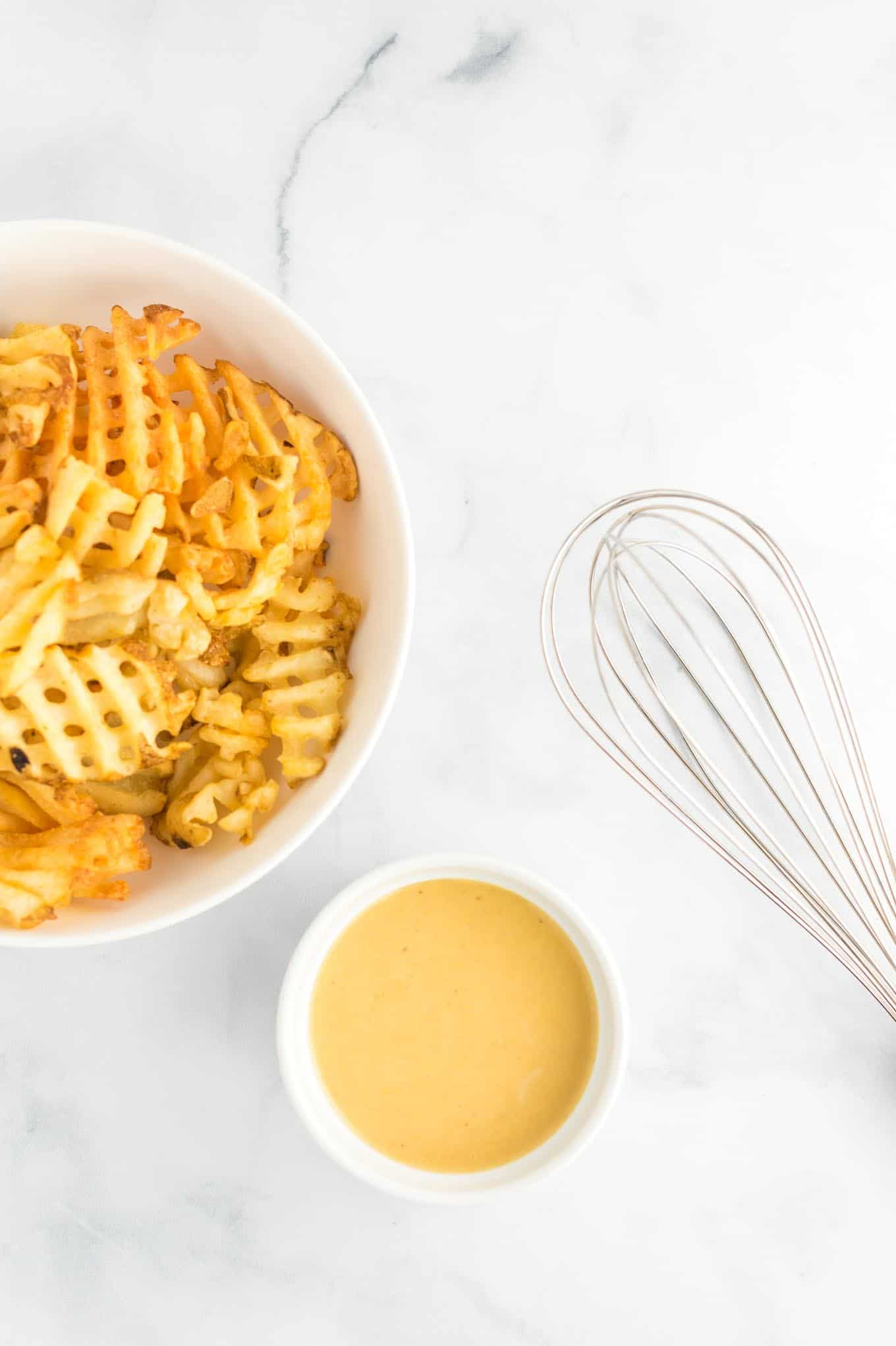 sauce in a white ramekin with fries in a bowl and a whisk