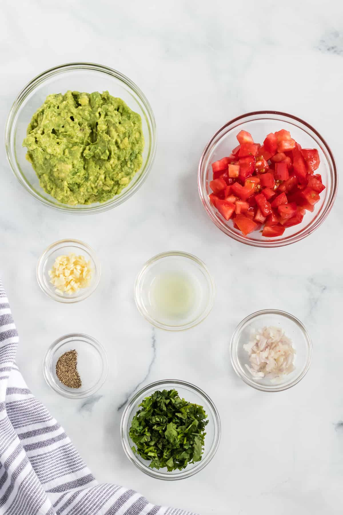 ingredients for guacamole with tomatoes in individual glass bowls