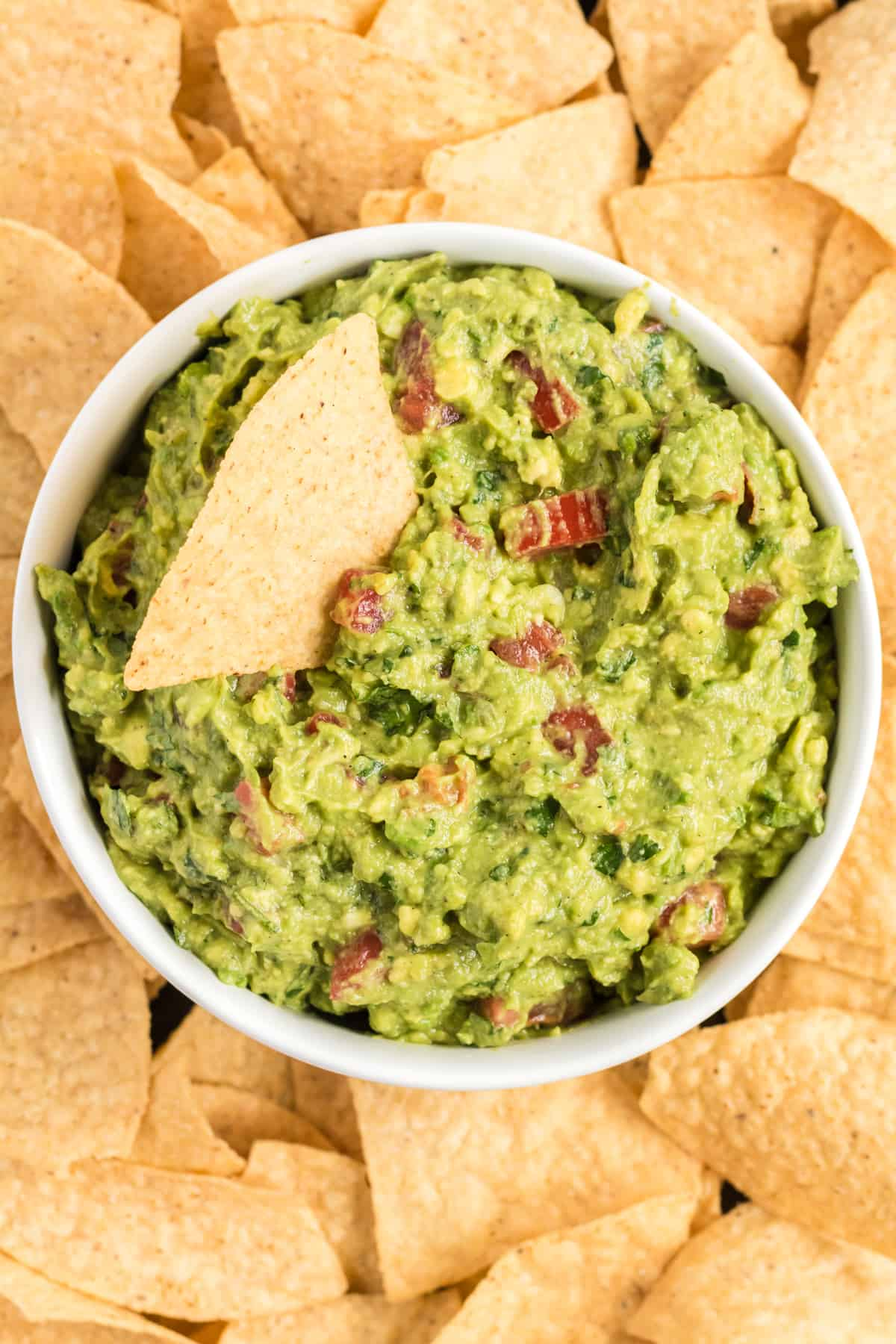 guacamole in a bowl on a platter surrounded by tortilla chips