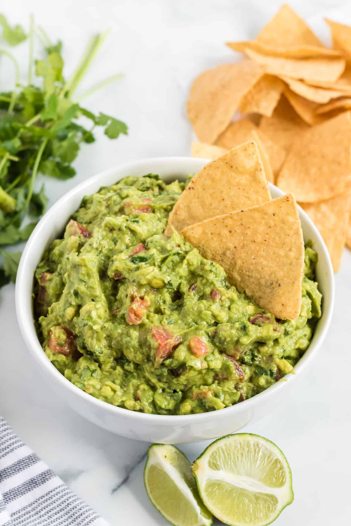 guacamole in a bowl with tortilla chips dipped in it