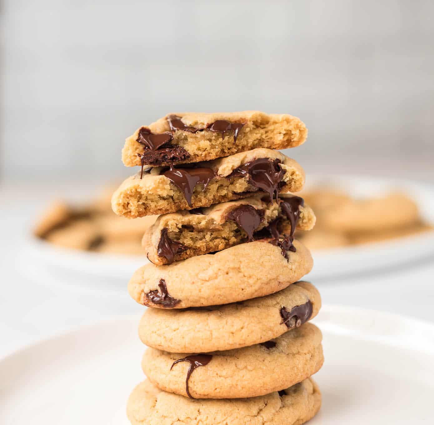 vegan chocolate chip cookies stacked with the top cookie split in half to show melted chocolate