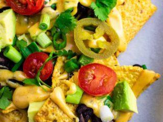 Loaded veggie nachos topped with homemade nacho cheese sauce. These are amazing! #veggienachos #vegetarian #nachocheese #nachocheesesauce