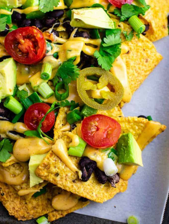 Loaded veggie nachos topped with homemade nacho cheese sauce. These are amazing! #veggienachos #vegetarian #nachocheese #nachocheesesauce