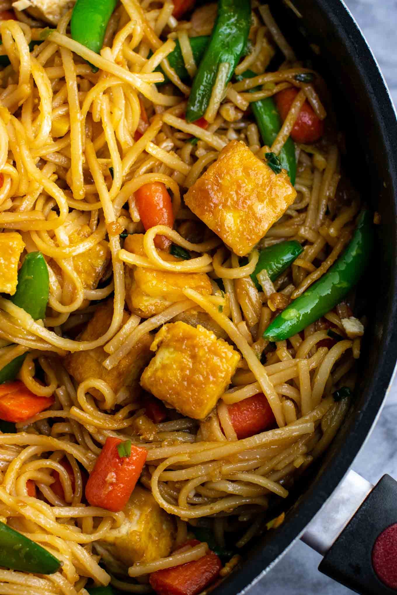 Vegan stir fry noodles with sugar snap peas and carrots. Homemade 3 ingredient stir fry sauce makes this taste amazing! #tofu #stirfrynoodles #stirfry #vegan #dinner #stirfryrecipe #vegetarian #tofustirfy