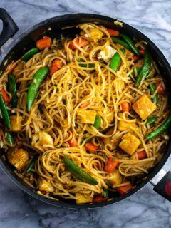 Vegan stir fry noodles with sugar snap peas and carrots. Homemade 3 ingredient stir fry sauce makes this taste amazing! #tofu #stirfrynoodles #stirfry #vegan #dinner #stirfryrecipe #vegetarian #tofustirfy