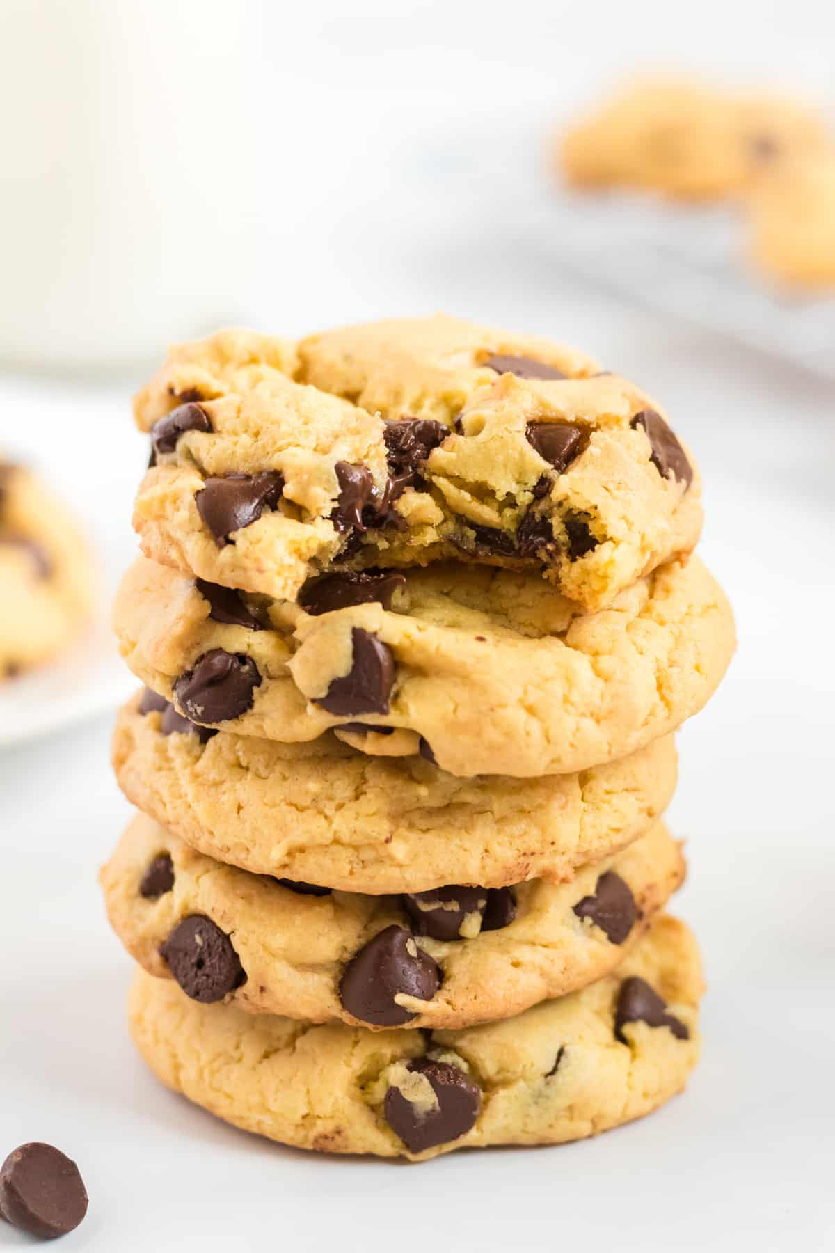 a stack of yellow cake mix cookies with the top one taken a bite out of