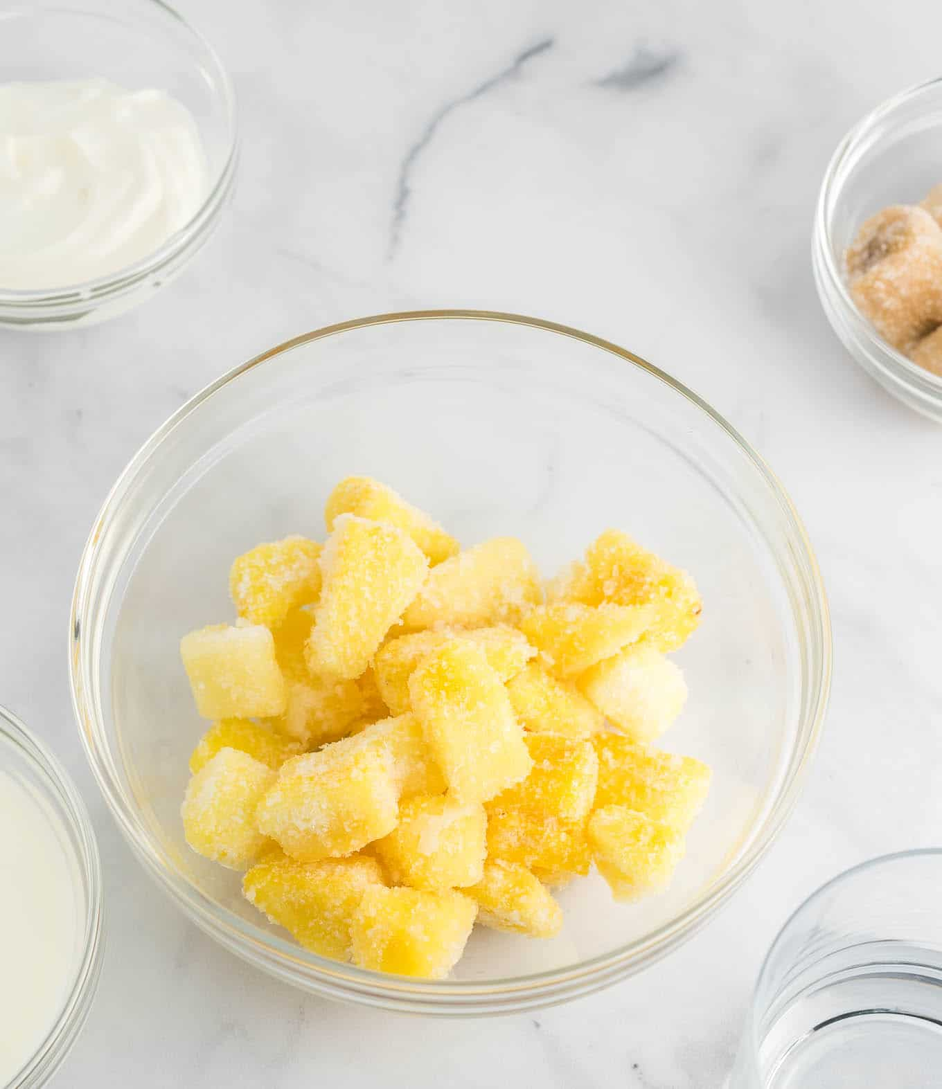 frozen pineapple chunks in a clear glass bowl